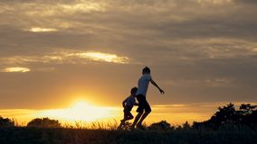 Silhouettes of running children in a field at sunset. Two children running and playing in the meadow at sunset stock video footage