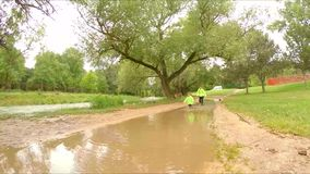 Two Children Running In Puddles In Park. In the frame there is a view on a park with green trees after rain with huge puddle in the centre and two children stock footage