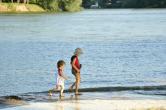 Two children running on the river bank Stock Photos