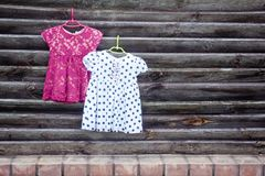 Two children`s dresses for girls on hangers.  stock photo