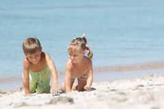 Two children on sand beach. Outdoor portrait of two children playing on beach Royalty Free Stock Image