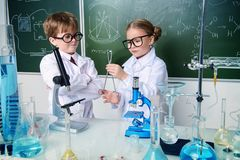 Two children scientists. Making experiments in the laboratory. Educational concept. Early development of children royalty free stock images