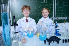 School children scientists. Two children scientists making experiments in the laboratory. Educational concept. Early development of children Stock Photos