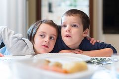 Two children see something in their home stock images