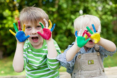 Two children showing painted hands outside. Two children showing their colorful painted hands royalty free stock photos