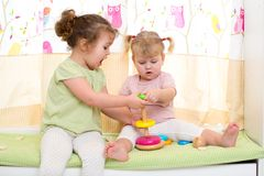 Two children sisters play together. Two cute children sisters play together indoor Stock Images