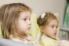 Two children sit on couch and look to right stock photo