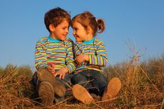 Two children sit on dry grass. Two children in striped T-shirts sit on dry grass Royalty Free Stock Image