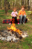 Two children sit near campfire Royalty Free Stock Image