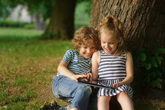 Two children sit in park under a big tree and play on the tablet. Stock Image
