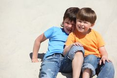Two children sit on sand Royalty Free Stock Photography