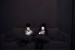 Two children, sitting in a dark, playing with gadgets Royalty Free Stock Images