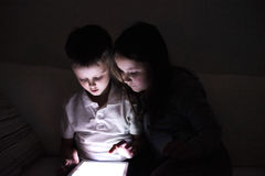 Two children, sitting in a dark, playing with tablet Royalty Free Stock Photography