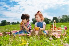 Two children sitting on picnic Stock Photos