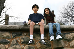 Two children sitting on rock ledge Stock Image