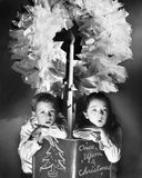 Two children sitting under a wreath holding a Christmas story book Royalty Free Stock Photos