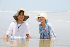 Two children sitting in water at ocean shore Stock Photos
