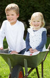 Two Children Sitting In Wheelbarrow Royalty Free Stock Photography