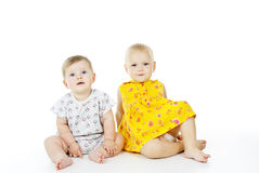 Two children sitting on a white background Royalty Free Stock Photo