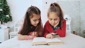 Two children sitting in a white room, reading a book in the background green tree. stock video footage