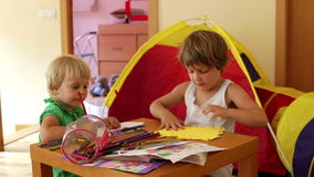 Two children sketching with paper and pencils. In home interior stock footage
