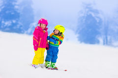 Two children skiing in snowy mountains Stock Photos
