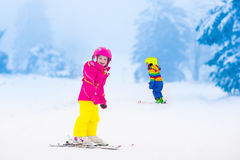 Two children skiing in snowy mountains Royalty Free Stock Photos