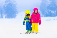 Two children skiing in snowy mountains Stock Images