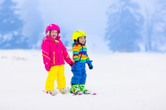 Two children skiing in snowy mountains Royalty Free Stock Image