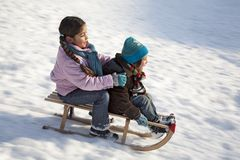 Two children on a sled having fun  Stock Photos