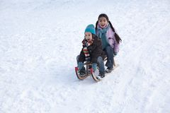 Two children on a sled having fun Royalty Free Stock Image