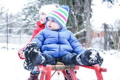 Two children sledding in winter. Two little children sledding together in winter in snow royalty free stock photos