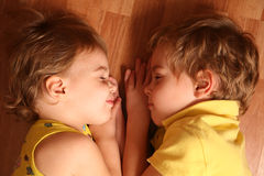 Two children sleep on floor Royalty Free Stock Photos
