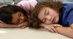 Two children are sleeping on the floor. In the lounge stock footage