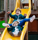 Two children  on slide at playground. Two children  in jacket on slide at playground area Stock Photos