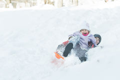 Two children sliding down snowy hill outdoors on orange plastic modern toboggan for kids Stock Photography