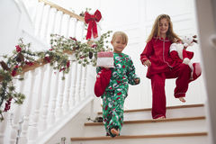Two Children On Stairs In Pajamas With Christmas Stockings Stock Images