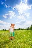 Two children stand together on a meadow Royalty Free Stock Images