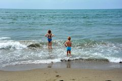 Two children  stand in the water on the beach and look at the sea Royalty Free Stock Photos