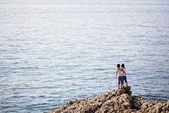 Two children, standing on rocks on the shore of the sea. Watching the passing boats Stock Photo