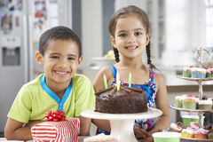 Two Children Standing By Table Laid With Birthday Party Food Stock Photography