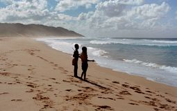 Two Children Stands on Shore Near Ocean at Daytime Stock Photography
