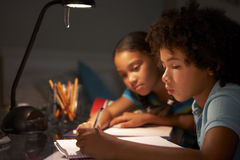 Two Children Studying At Desk In Bedroom In Evening Stock Image