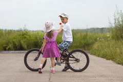 Two children in summer day bicycle and flower boy and girl Royalty Free Stock Images