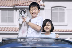 Two children on the sunroof with dog. Happy two children standing on the sunroof of the car while holding little siberian husky puppy and smiling at the camera Royalty Free Stock Image