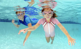 Two children swimming underwater in pool. In pink and blue Royalty Free Stock Photography