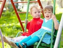 Two children on swing Stock Photo