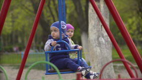 Two children on swing in spring park. Outdoors stock footage