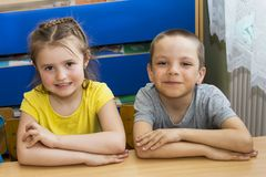 Two children at the table. cute elementary school kids in a classroom. A boy and a girl are sitting at the table. Portrait of royalty free stock photography