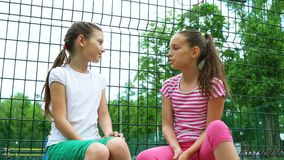 Two children telling secrets and laughing in park, outdoors. Leisure time park stock video